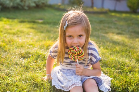 thrilled: cute little girl eating a lollipop on the grass in summertime.