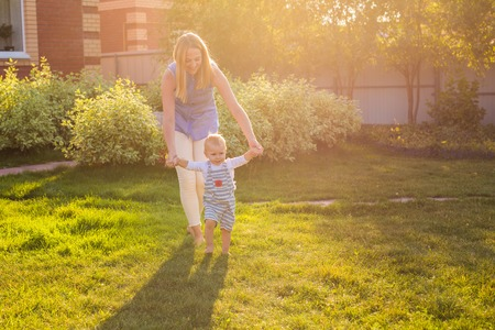 beautiful mother is walking on with her little baby boy son with first steps Stock Photo