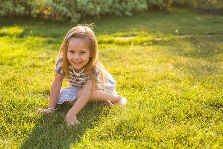 Ragazza felice del bambino che gioca sul prato in estate in natura.