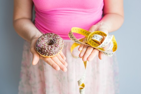 Close-up of womans hands holding a donut and a measuring tape. The concept of healthy eating. Diet.