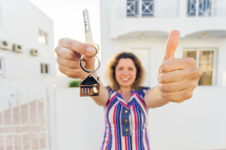 Concept of housewarming, real estate, property and moving - New home owner with key Stock Photo