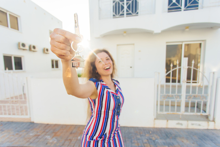 front house: Happy young woman In Front of New Home with New House Keys Stock Photo
