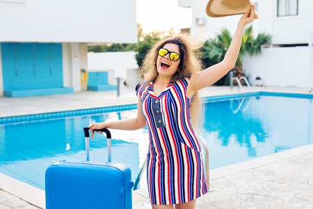 Happy young woman with blue luggage arriving to the resort. She is walking next to the swimming pool. Beginning of summer vacation concept. Stock Photo