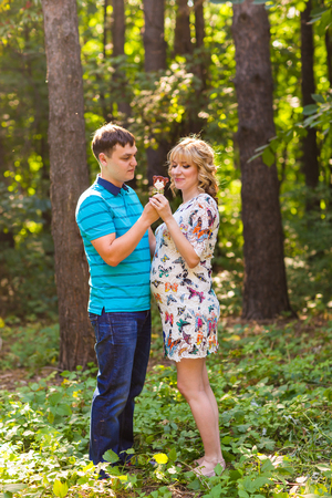 Happy young pregnant couple hugging in nature Stock Photo