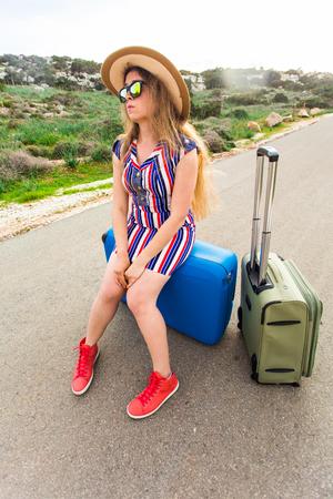 Betonte junge Touristenfrau sitzt auf Radtasche