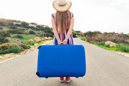 Beautiful young lady travelling with a blue suitcase, rear view