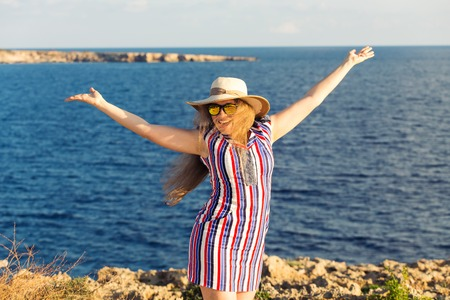 resort life: Portrait of young woman on the beach near the sea with hands up wearing dress and hat