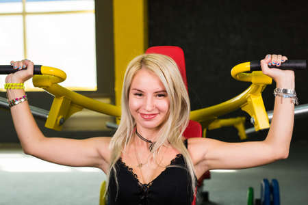 fitness, sport, powerlifting and people concept - Young woman weight training Stock Photo