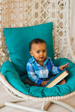 Portrait of African American baby boy holding book on sofa Stock Photo - 81837858