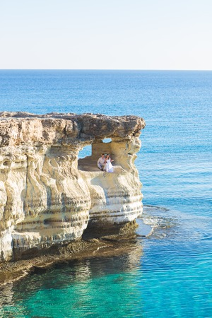 beautiful gorgeous bride and stylish groom on rocks, on the background of a sea, wedding ceremony on cyprus