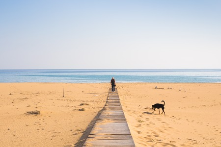 Man with dog walking on the wooden path on the beach and looking into the distance of the ocean Stock Photo