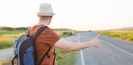 Young caucasian man seen from behind carrying a backpack hitchhiking in a minor road, with his thumb up