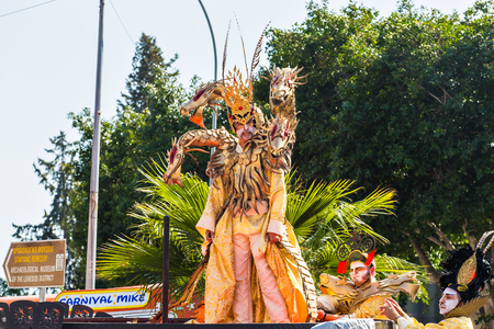 flower parade: LIMASSOL, CYPRUS - FEBRUARY 26: Carnivalists in a silver cylinder hats joyfully follow the Limassol Municipality Band during the annual Carnival Parade, February 26, 2017 in Limassol
