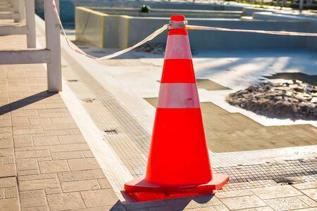 Plastic striped orange cone on the road. Traffic cone