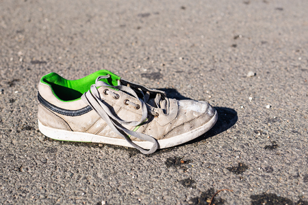 Poverty concept - Thrown out on the street dirty ragged sneaker