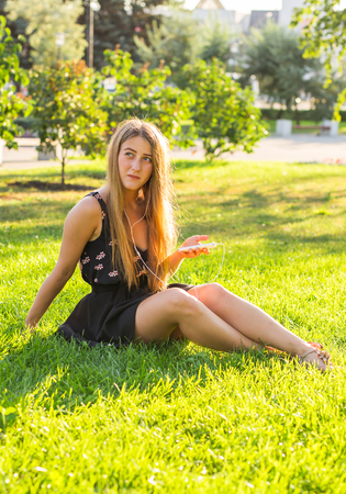 Beautiful girl sitting on the grass in the park and listen to music