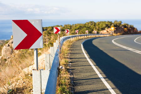 Right Turn Sign: Road signs warn of a sharp turn on a narrow road Stock Photo