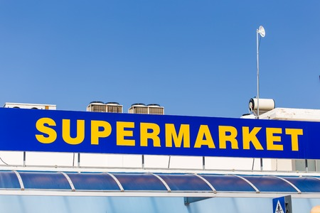 fasade: Supermarket sign on building. Yellow and blue inscription supermarket