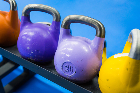 Many colorful dumbbells are on stand at the gym.