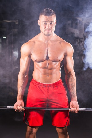 Young handsome bodybuilder sportsman working out with a barbell in gym, doing biceps training, close up
