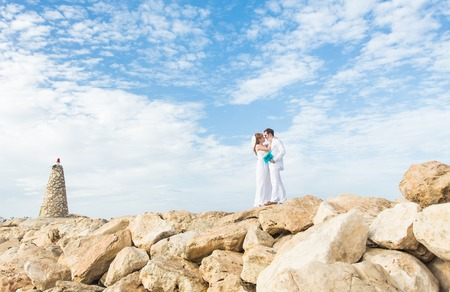 Wedding couple standing on the cliff. Groom tenderly embraces the bride. Stock Photo
