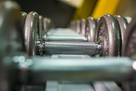 staying fit: Dumbbells in gym. Close up many dumbells in sport fitness centre
