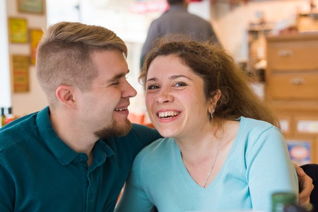 Portrait of laughing caucasian couple enjoying date in cafe
