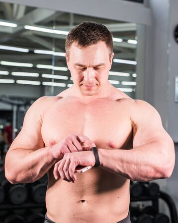 young man using fitness bracelet during sports training in the gym