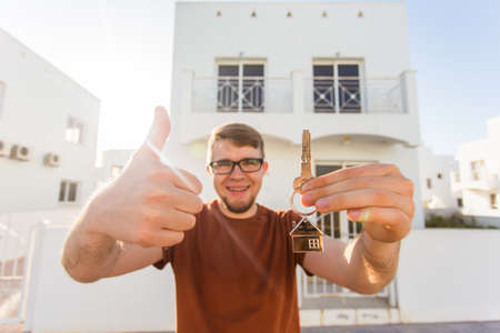 real estate house: New home, apartment, owner and people concept - Close up of keys that showing young happy man with new home on background Stock Photo