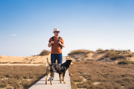 Outdoors lifestyle image of travelling man with cute dog. Tourism concept. Standard-Bild