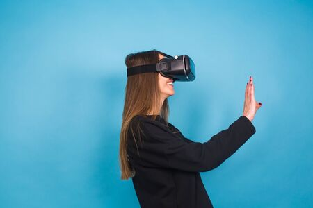 Happy young woman using a virtual reality headset on blue background