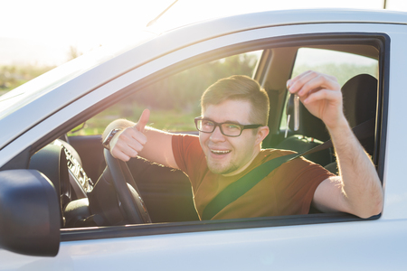 Young driver showing car keys and thumbs up happy. Man holding car key for new automobile. Rental cars or drivers licence concept with male driving in beautiful nature on road trip.
