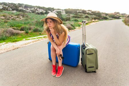 a situation alone: Sad woman sitting on suitcase