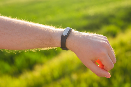 Sport, gadget, activity tracker and people concept - Close up of runner jogging outside looking at his wearable fitness bracelet.