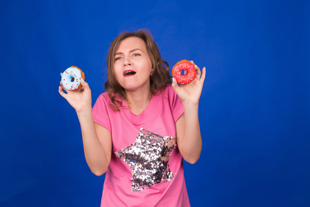 donut style: beautiful young funny girl with donuts on blue background. Unhealthy diet, junk food, party and celebration concept