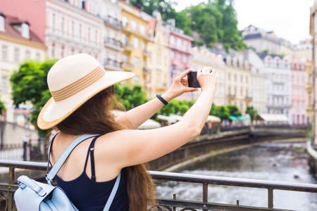 Woman taking pictures with smartphone. Stylish summer traveler woman in hat with camera outdoors in european city, old town Karlovy Vary in the background, Czech Republic, Europe Stock Photo