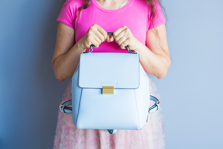 Close up stylish woman in pink skirt with blue bag. Fashion concept.