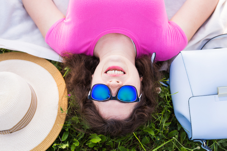 Top portrait of young woman laying on the grass in the park