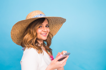 Technology, people and modern devices concept - Close up of woman writing in phone, texting message side view on blue background with copy space. Stock Photo