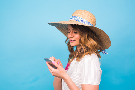 Technology, people and modern devices concept - Woman writing in phone, texting message side view on blue background with copy space. Stock Photo