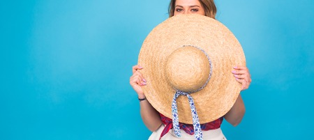Beautiful young woman wears in summer dress and straw hat is laughing on blue background with copy space Stock Photo