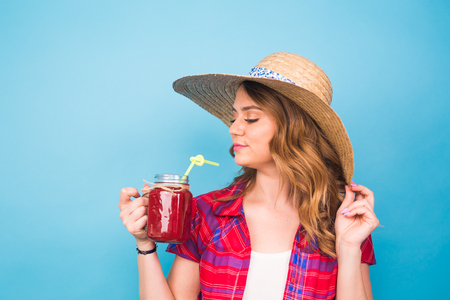 smiling woman drink red juice. studio portrait with blue background and copy space
