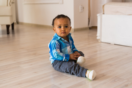 Small child tries to put on his shoes. Mixed race baby boy with shoes 版權商用圖片