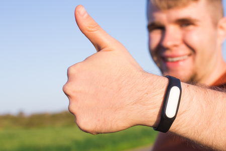 fitness, sport, training and lifestyle concept - close up of young man with heart-rate watch bracelet in summer park.