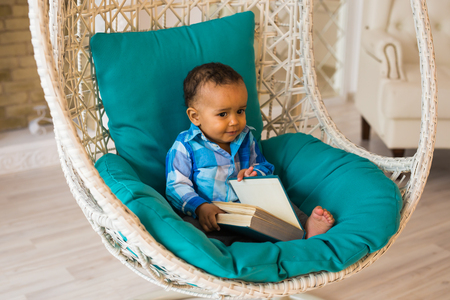 Portrait of African American baby boy holding book on sofa Stock Photo