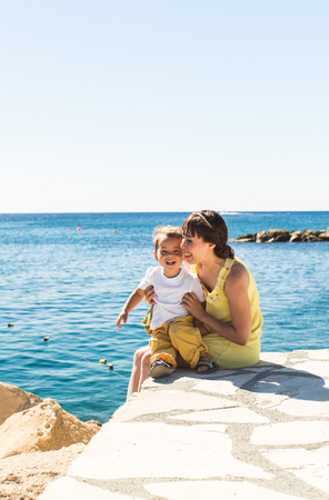Happy family, friends forever concept. Smiling mother and little son playing together near sea.