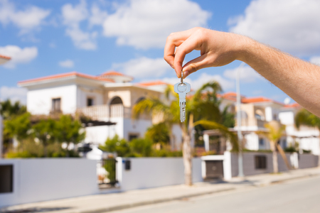 Holding house keys on house shaped keychain closeup in front of a new home. Concept of real estate
