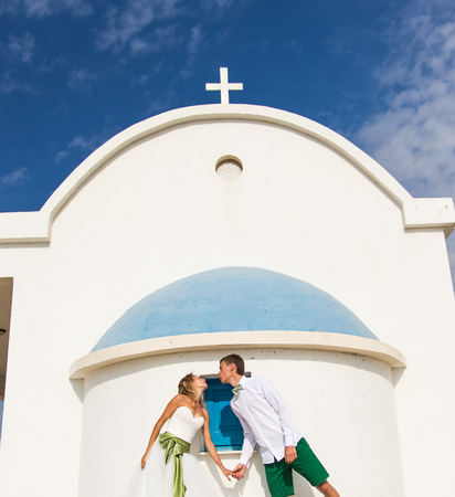 Funny beautiful bride and groom with a church on the background