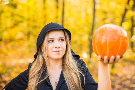 portrait of dramatic beautiful blond young woman holding pumpkin in forest. Halloween day. Stock Photo