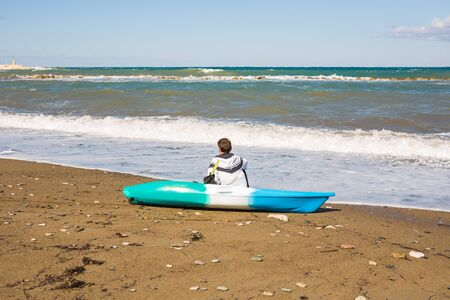 Young caucasian man sitting on beach with kayak, back view Stock Photo